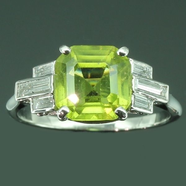 Art Deco platinum diamond ring with peridot  1920's Platinum, diamond and peridot ring with typical architectural Art Deco design. The central square emerald cut peridot is flanked left and right by three baguette cut diamonds. C 1920