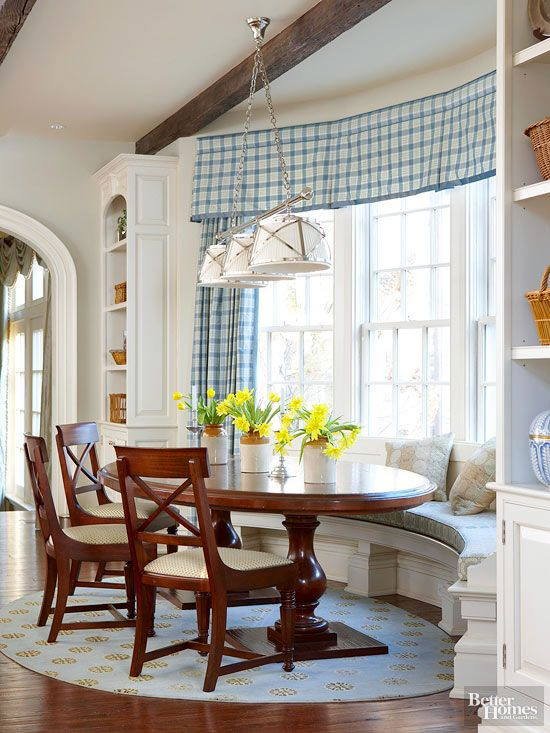 This home's rounded window wall offers the perfect shape for a spacious banquette. The oval table echoes the gentle curve of the bench, which fits snugly between two built-in display units. Additional chairs easily accommodate more guests and can be moved to transform the table into a buffet area while entertaining./