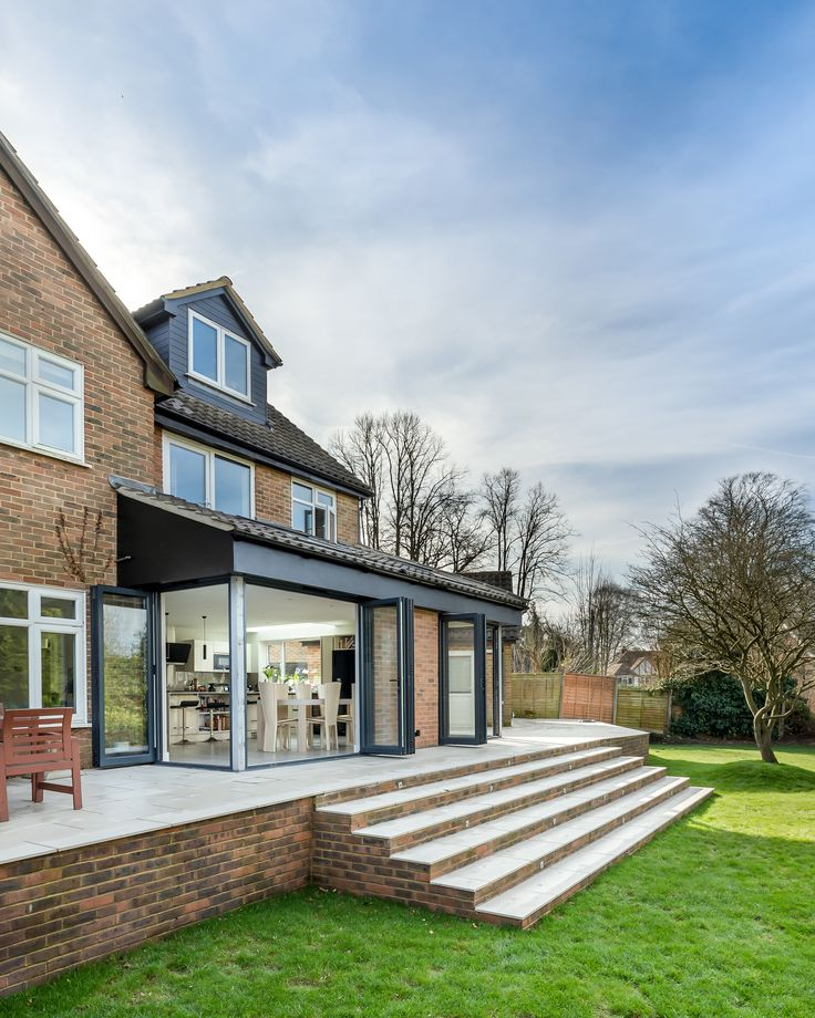 Rear extension | sloped roof | corner openings | bi-fold doors | raised patio | garden levels | landscaping | external steps | feature tree | 2-storey extension | pitched roof dormer