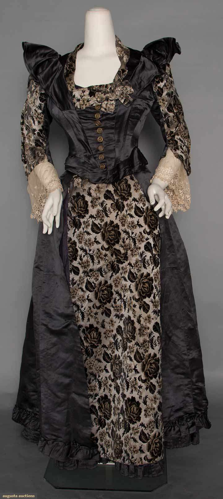 "CUT VELVET DINNER GOWN, c. 1892 2-piece, dark grey silk satin bodice & trained skirt, grey & taupe floral velvet cut to silver-grey satin sleeves, trim & CF skirt panel, 3/4 sleeves w/ lace flounces, 9 CF brass buttons, B 37"", W 32"", Skirt L 39""-52"" Suddon-Cleaver Costume Collection"