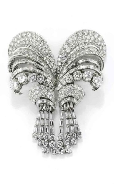 DIAMOND BROOCH BY BULGARI, upper element consists of two swirls pave set with diamonds, baguette cut diamonds and brilliants, two pendants with pavé diamonds which fall in fringe articulated baguette-cut diamonds with brilliant ending; divides to form a pair of clips, also wearable as a single pin, and a pair of dangling earrings, end 1940 the signed Bulgari