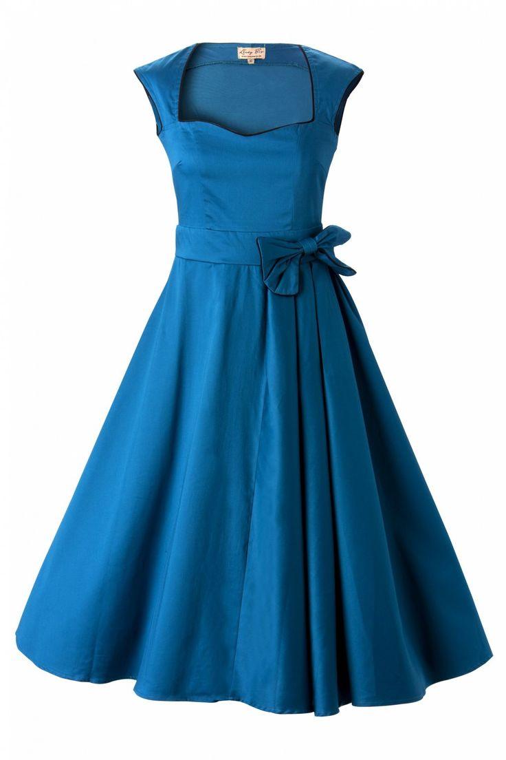 De1950's Grace Blue Bow vintage style swing party rockabilly evening dress van Lindy Bopis een prachtige classy swing dress met speelse accenten! Geïnspireerd op de elegante jaren 50 stijl van Grace Kelly.De wijde semi sweetweart halslijn en kapmouwtjes zijn afgewerkt met een pittig zwart biesje. Net boven je taille is de jurk voorzien van een feestelijke grote strik extra geplooid en vanaf daar loopt ze uit in mooie volle cirkelrok. Wijd genoeg om zonder pett...