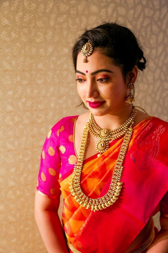 South Indian Brides - Orange Kanjivaram Sari with Pink and Gold Silk Blouse and Gold Rani Haar | WedMeGood | Gold Maangtikka and Gold Traditional Necklace  #wedmegood #kanjivaram #south #indian