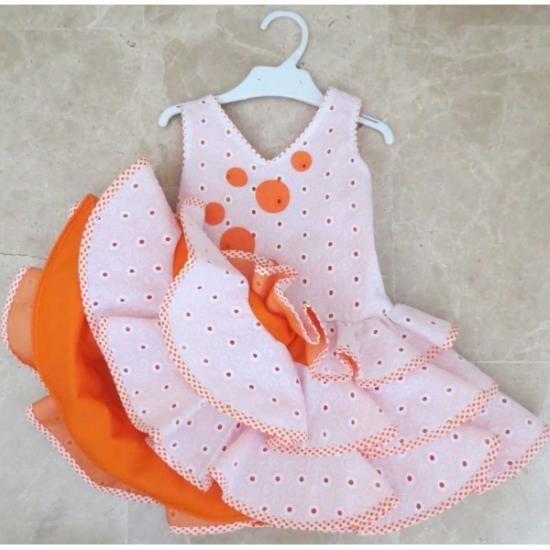El proceso de fabricación de cada traje de flamenca es artesanal. Traje de gran calidad y diseño con las mejores garantías. La confección del traje es bajo pedido, por eso el plazo de entrega es de 15 días.  El traje esta confeccionado en tira bordada y viveado en blanco con lunares naranjas. Cuerpo con lunares naranjas