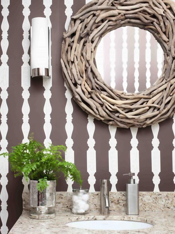Found objects like driftwood look especially current when surrounded by a modern space. A round mirror bedazzled with patinaed driftwood twigs lends an organic vibe to this graphic powder room.