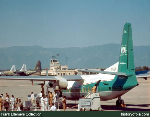 Pakistan International Airlines (PIA) Fokker F27 Friendship (AP-ALX) at Rawalpindi Airport in 1960s. Pakistan Air Force (PAF) Lockheed C-130 Hercules at PAF Base Chaklala also visible in the background.  The airfield is now known as Benazir Bhutto International Airport - Islamabad/PAF Base Nur Khan - Chaklala.