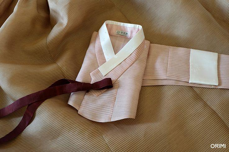 차분하고 우아한 분위기가 물씬 나는 항라 원단의 이 한복은 오리미의 친정어머니 혼주한복입니다. 은은한 색감이 매력적인 한 벌이에요.  바탕색만 놓고 보자면 굉장히 연한 색으로만 이루어진 한 벌이지만, 환한 연분홍 저고리와 연황토색 치마에 모두 고동색 항라 무늬가 들어가 있기 때문에 옅은 색감 위에 한 겹 무게감을 더한 느낌입니다.  게다가 이 갈색 항라 무늬는 자세히 보면 아주 얇은 선이 여러 겹 겹쳐서 짜여진..