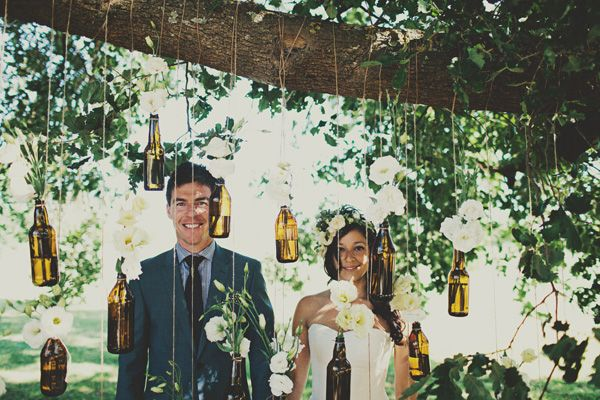 hanging bottles of flowers from trees - backdrop to photos from rockmywedding.co.uk