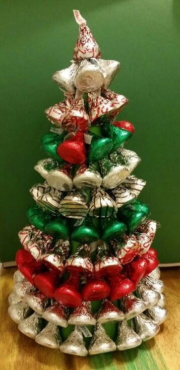 Simple and edible Hersey kisses and hugs chrismas trees.  1. Get any paper and kisses you choose. 2. Make the paper into a cone and trim so cone sits flat. 3. Glue on kisses.( I used low heat glue gun) A few small tricks I learned. Put the cone on a water bottle it holds the trees up higher. Glue tip and a little done the side, place glue on kiss.   I have seen these trees before and they look cute with just the kisses or you can throw some ribbon on toppers on them too.