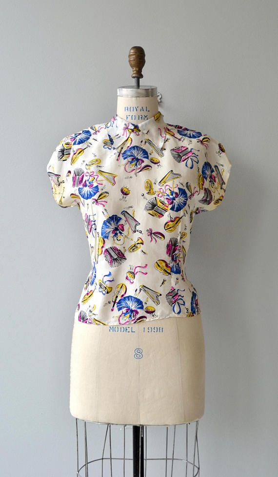 Vintage 1940s white silk blouse with brightly colored music and dancer print, small collar, short dolman sleeves, waist darts and back buttons. --- M E A S U R E M E N T S --- fits like: medium shoulder: 16 bust: 41 waist: 33 length: 21 brand/maker: n/a condition: discoloration under arms and two faint spots on bust ➸ More tops & sweaters https://www.etsy.com/shop/DearGoldenVintage?section_id=5800171 ➸ Visit the shop http://www.DearGolden.e...