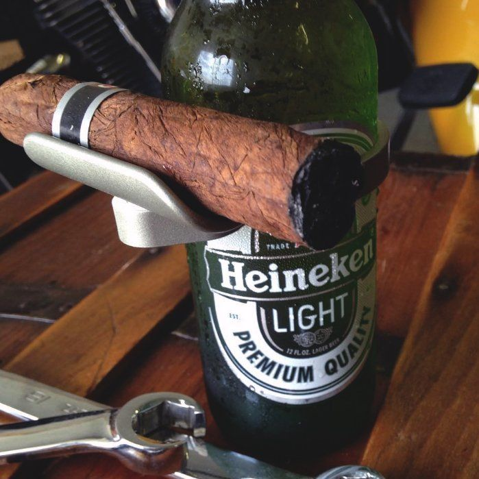 CigarzUp Cigar HolderAn ingenious invention that clasps easily to a bottle of beer and acts as the perfect cradle for your cigar!The next time you're poolside, at the beach, or just relaxing at an outdoor cafe, CigarzUp is ready to mind your cigar for you.