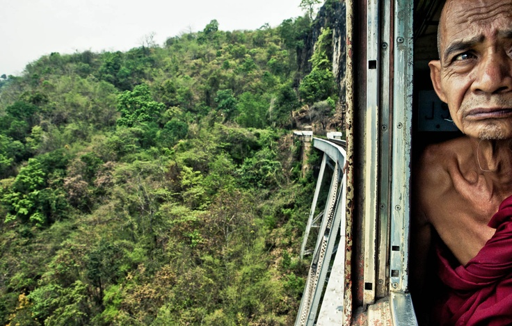 A monk on a train crossing the 689-meter Goteik viaduct, built by the British in 1900 - railway between Pyin U Lwin and Lashio, Burma (Myanmar)