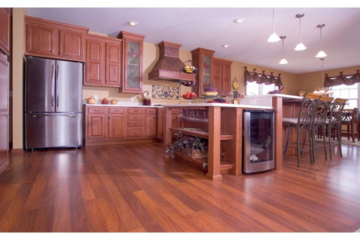 Nice dark wood flooring with dark wood cabinets.  Large island with wine cooler and all stainless steel appliances.  Nice large and open kitchen with decorative range over stove.