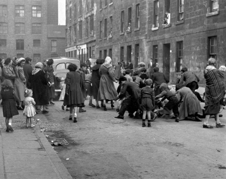 "A ""scramble"" in Gemmel Street, Bridgeton, 1955. Scrambles were a tradition at weddings in many parts of Scotland, when neighbours turned out to see the bridal party leave the street on its way to the church. Coins were thrown from the wedding car (usually by the father of the bride) as it drove off and children scrambled to pick up as many as they could."