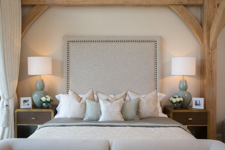Crowning this magnificent master bedroom in our modern Surrey barn; this stunning bespoke headboard is made in a calming, neutral tone fabric with stylish studded border, perfectly complemented by these elegant Zoffany and Casamance cushions.