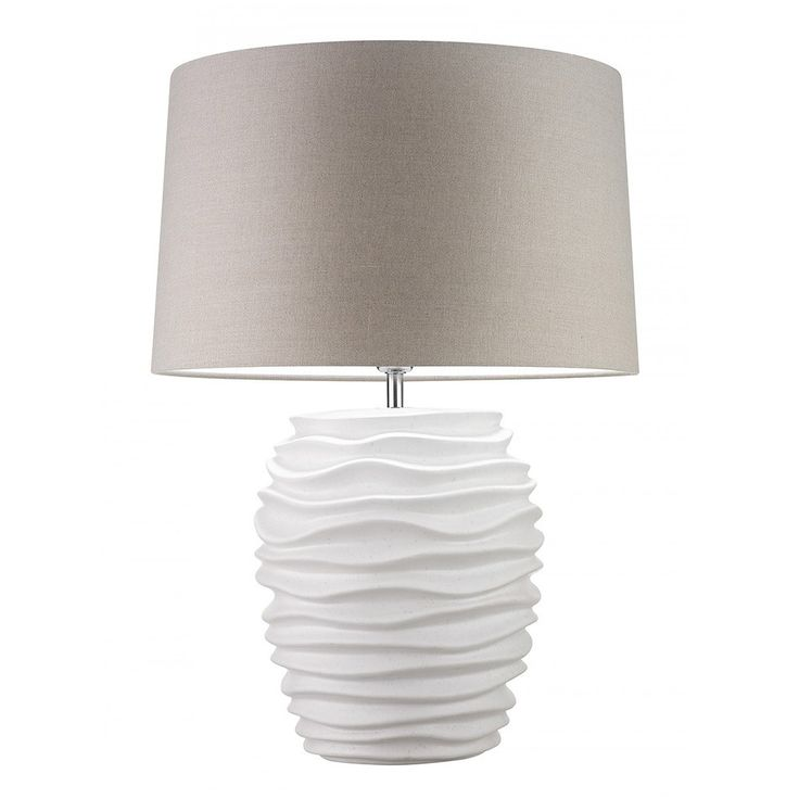 Make a spotless addition in a Trier White Pebble Matt Lamp. From Heathfield & Co, the body of the lamp comes in an antiqued ivory semi matt glaze with a subtle ripple pattern that offers a simple look and feel to the piece. The lamp is finished with an 18-inch Roman drum shade in an oatmeal linen finish with white PVC lining that offers an immaculate look to the lamp. Place yours in the living area, hallway or bedroom of your home for piece that will enhance the surroundings. The Heathfield…