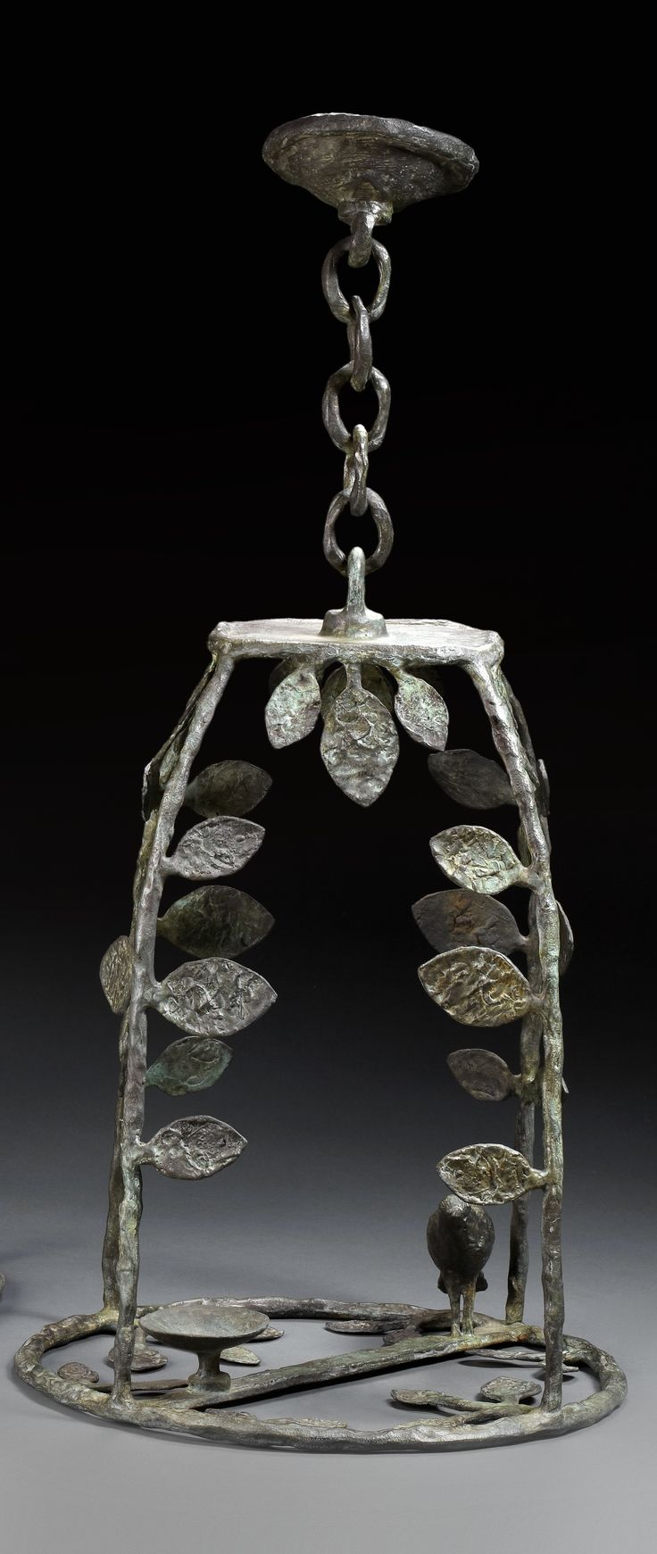 Diego GIACOMETTI (1902-1985) Hanging lantern  Bronze with antique patina. Model with four posts decorated  to resemble leafy branches, a bird is perched on a branch  with a small cup on the round base. 31. 8 x 16.1 in. - 81 x 41 cm.
