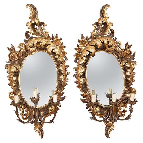 Raro par de espelhos/arandelas, emoldurados por madeira entalhada e dourada a ouro brunido <br /> em formato de grande folha. Três braços para luzes. 58 x 110 cm de altura. <br /> Itália, séc. XIX.