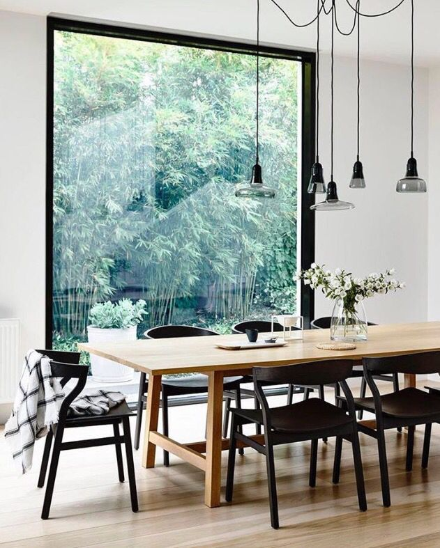 wood table with black chairs, wood floor and white walls, big window with black frame, black light fixtures, i probably want a woven / basket fixture over the table though.