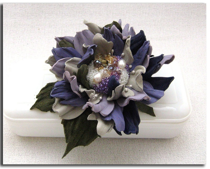 Handcrafted leather brooch and hair clip in mixed colours. It has been treated to hold its shape. The centre of the flower is decorated with...