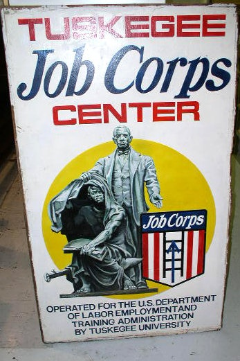 "Hand Painted Tuskegee Job Corps Center Sign. 59.5""X35.5"" plywood, painted on both sides. An exceptionally fine illustration of Booker T. Washingon ""lifting the veil of ignorance"" from the head of a freed slave by showing him the ways to a better life. The slave, holding a book, crouches on a plow and anvil which represent tools of agriculture and industry. Signed on both sides ""Vince Morgan"" $2500"