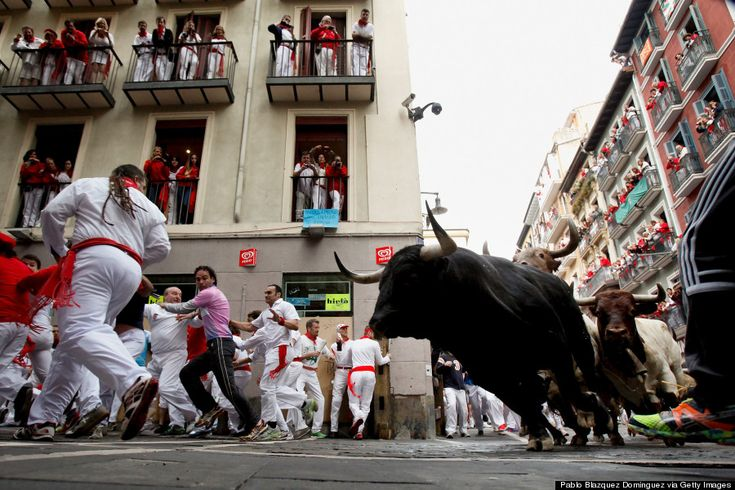 PAMPLONA, SPAIN - JULY 10: Revellers run with Garcigrande's fighting bulls along the Curva de Estafeta during the fifth day of the San Fermin Running Of The Bulls festival on July 10, 2014 in Pamplona, Spain.
