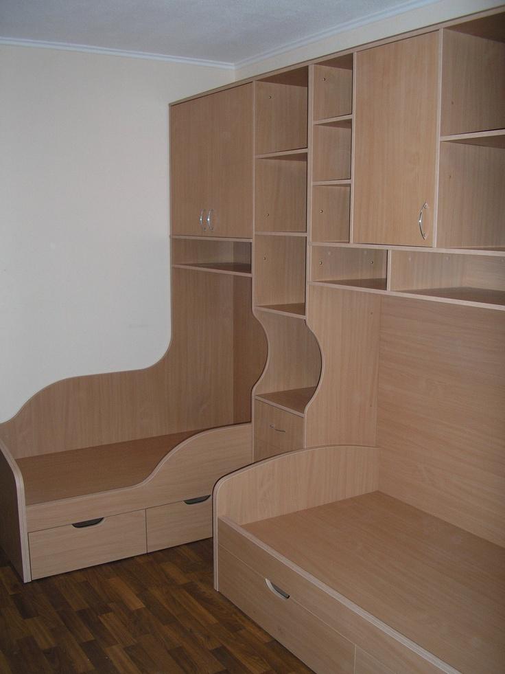 Мебель для детской комнаты, рассчитанной на двух детей. Выполнена в виде единой конструкции из двух кроватей с выдвижными ящиками и шкафов.