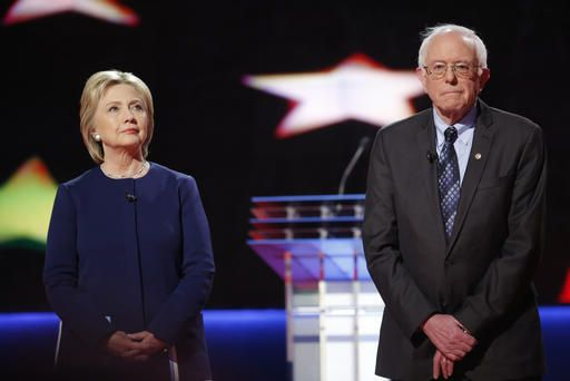Democratic U.S. presidential candidates Hillary Clinton and Bernie Sanders pose together onstage at the start of the U.S. Democratic presidential candidates' debate in Flint, Mich. on March 6, 2016. (Photo by Carlos Barria/Reuters)