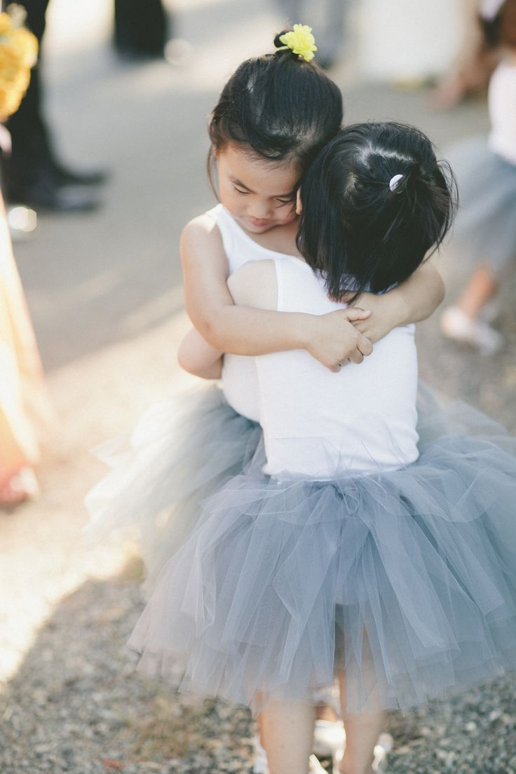 awww -- sweet hugs. Tutus for flower girls -- onelove photography - onelove-photo.com -- See the wedding on #SMP here: http://www.StyleMePretty.com/california-weddings/2014/04/07/rustic-wedding-with-pops-of-yellow-at-park-winters/