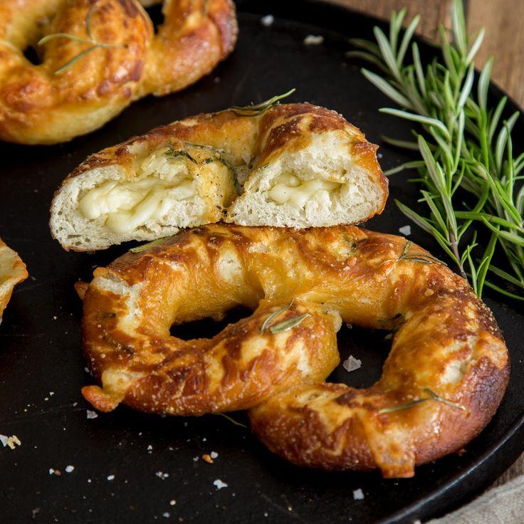 Zuerst geben wir etwas Rosmarin in den Teig, dann Mozzarella und Parmesan in die Füllung und zum Schluss Butter und Knoblauch obendrauf.