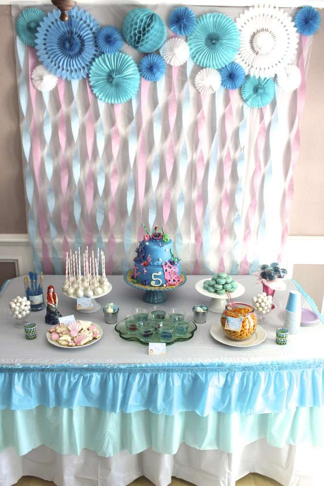 Pretty dessert table and backdrop at a mermaid girl birthday party! See more party planning ideas at CatchMyParty.com!