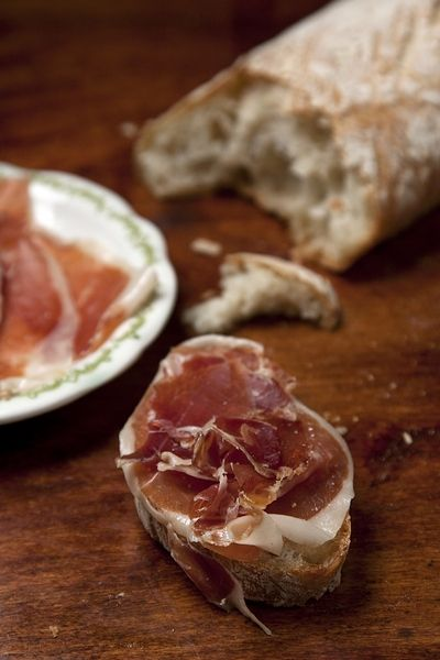 Serrano Ham: the renowned Spanish take on prosciutto — a dry-cured ham that's sliced thin enough for the soft fat to melt on the tongue — cures in salt for two weeks, and then is stored in towering piles for upwards of two months. The resulting ham, flat and dense from the pressure of being stacked, is sweet and fatty.