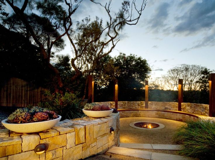 Eco Outdoor Killcare random ashlar sandstone walling curved retaining wall around outdoor fire pit, Joanne Green Landscapes. Eco Outdoor | Joanne Green Landscapes | Killcare random ashlar sandstone walling | livelifeoutdoors | Outdoor design | Natural stone walling | Garden design | Outdoor paving | Outdoor design inspiration | Outdoor style | Outdoor ideas | Garden ideas | Retaining wall | Stone veneer | Stone walling | Stone cladding | Luxury homes |  Natural stone paving | Outdoor tiles…