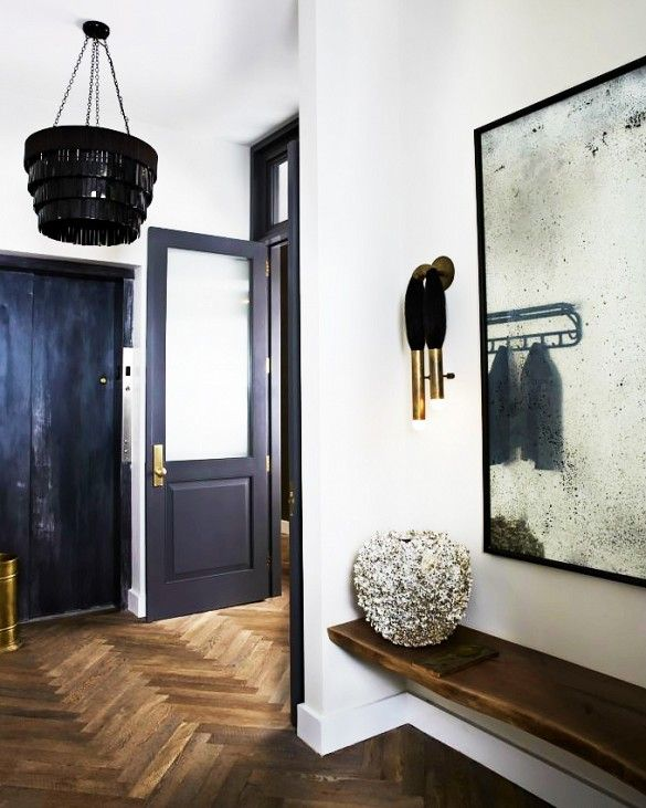 Black and white minimalist entryway with black chandelier and black and gold wall sconce
