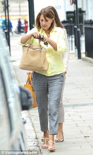 Carole fumbles in her bag as the pair enjoy the last of the sun in London on…