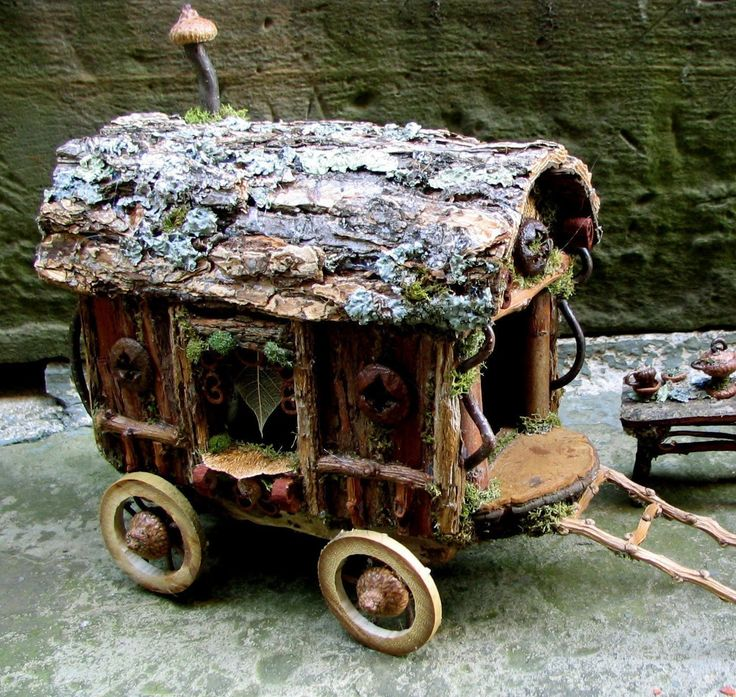 """Fairy Travelers Caravan Custom OrderA traditional caravan for traveling wee folk composed of all natural materials such as birch and sycamore bark siding, shelf fungus driver's seat, and acorn and twig wheels. Windows and entries are surrounded by decorative details of curly twigs, buckeye hulls, acorns and pods. Body of caravan is approximately 8"""" high x 6"""" wide x 10"""" long, with horse harness frame extending another 6"""" outward from front. $250.00"""