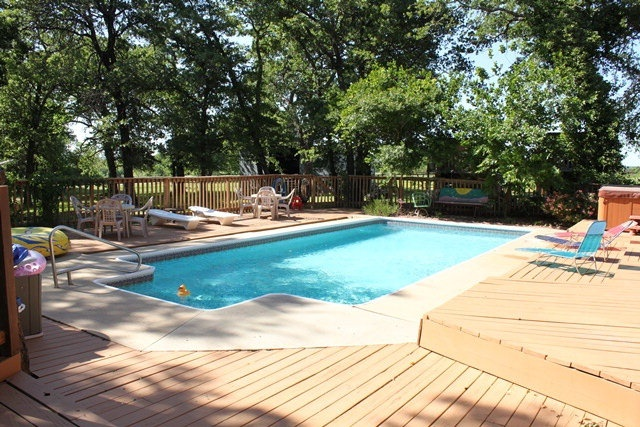 Stamped concrete bordered by trex pool deck to replace for Pool wood deck ideas
