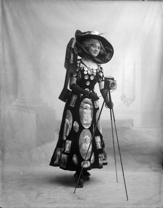 Ref: 1/1-021275-G  Woman advertising Wanganui's Telsa photographic studios, circa 1910. She wears a hat with a sign reading `Tesla Studios', a dress covered with photographic prints, and roller skates. She holds a camera on a tripod. Photograph taken by Telsa Studios, which operated 1908 to 1955. This photo might be of Miss M Burden who tied for Best Poster Costume at a fancy dress and poster carnival held at the Olympia Rink, Hastings, March 1912.