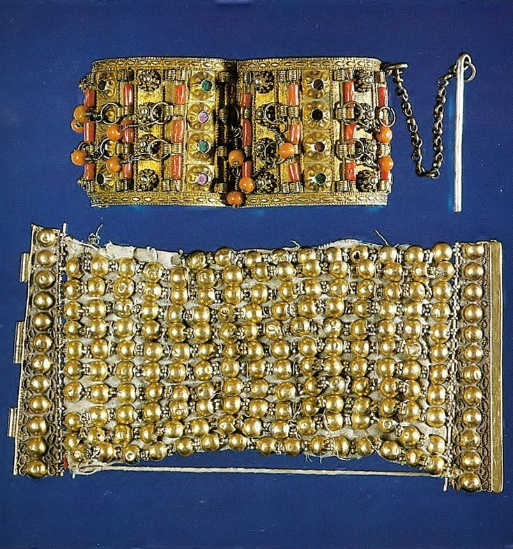 Two bracelets.  Late-Ottoman, from Anatolia, 19th century. Top: handcuff-formed white metal bracelet, gold gilded.  With corals and green & pink stones set in a blossom-shape.  Width: 58 mm. Bottom: 18-carat gold.  11 rows of half globes, affixed to each other and sewn to the white linen tissue.  With a quadrangle closing-plaque, adorned with globes.  10 x 20 cm. (both: Ankara Ethnographic Museum).