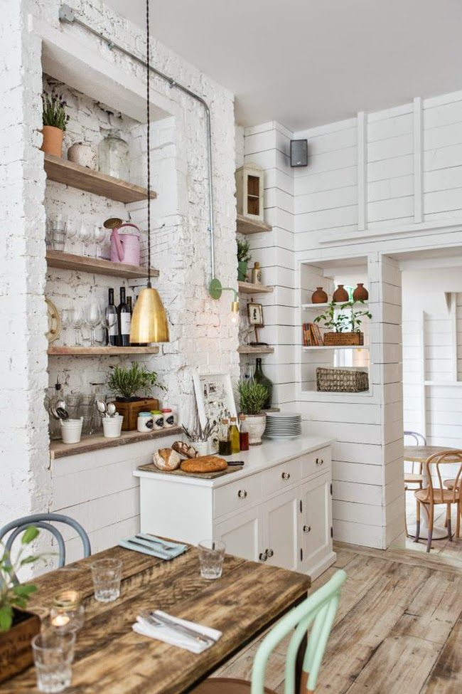 White and light wood kitchen with a brass pendant lamp, mint chair and pink watering can