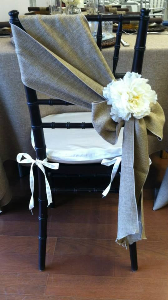 A simple burlap chair sash with a flower on the bow - love this idea, a different take on the usual chair coverings! #wedding #westcountry #rustic