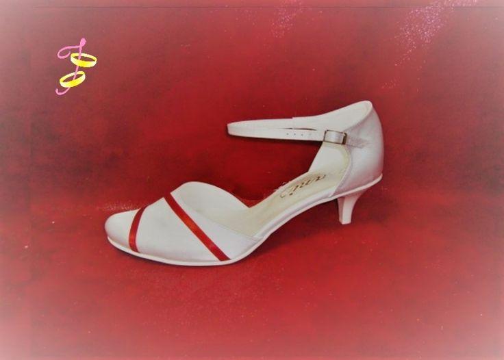 Bruidsschoenen met rode lint. Met enkelbandje voor extra steun. Verkrijgbaar in de kleur: wit, roomwit of ivoor. Maten: 33-43.Mogelijke hak hoogtes: 1.5 cm  - € 89,00