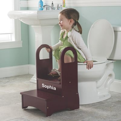 "MY STEP UP STOOL: This sturdy wood step stool has tall side handles that help kids keep their balance while climbing and perched on the toilet. Great for reaching the sink and big kid beds, too! Gives children confidence while potty training and washing up; makes an infinitely useful household stool later. MDF wood, with stable, non-slip base. Two-step stool is 13""L x 14""W x 10""H, topped by 12""H handles..."
