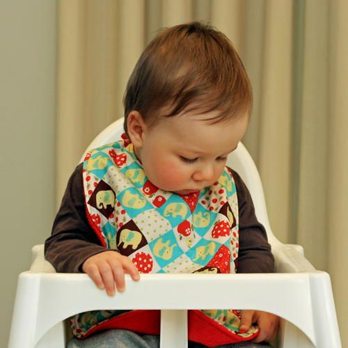 """This bib is huge! It's long and wide and has snaps to transform it into a pelican pocket style bib. Great for babies first starting solids."""