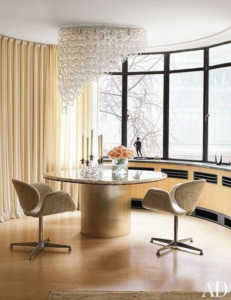 A dining area featuring a custom-made light fixture is composed of vintage Vistosi glass | archdigest.com
