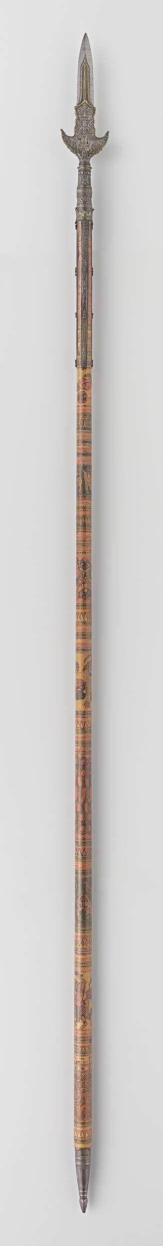 | Partizaan van het wapenrek door Indische groten geschonken aan Gouverneur-Generaal J.C. baron Baud, c. 1700 - c. 1800 | Ronde houten schacht beschilderd in zwart, rood, geel en groen met voorstellingen van Boddhisattva's, menselijke figuren en geometrische motieven. Onderzijde schacht heeft ijzeren kegelvorm met geschulpte rand en toelopend in stompe vierkante punt. Brede kling uitlopend in scherpe punt, met vier lippen. Kling is rijk versierd in reliëf met boddhisattva's en bloem- en…