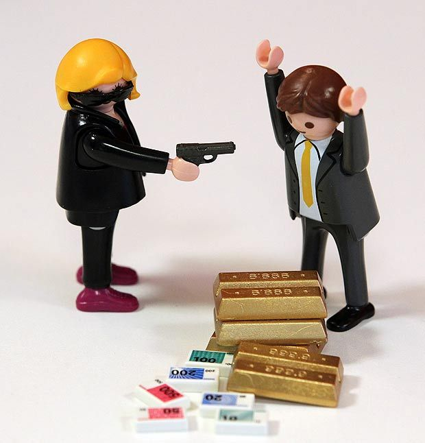 Playmobil bank robbery set including a sunglass wearing blond robber and terrified bank clerk.