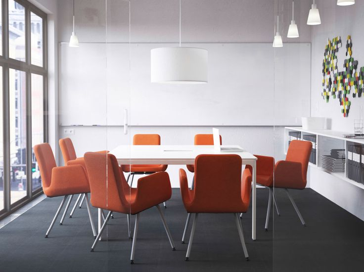 A meeting room with a white conference table and chairs with dark orange wool cover