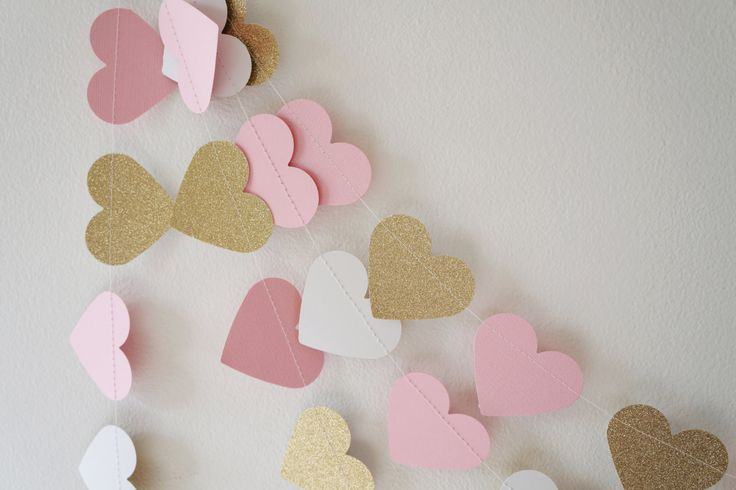 Hang our Pink and Gold Lux Heart Paper Garland for some sparkle! Our garland has soft pink and gold tones with just the right amount of glitz. Materials include shimmery light pink card stock paper and light gold glitter paper. Machine-sewn with white thread. There is a gold hanging ribbon