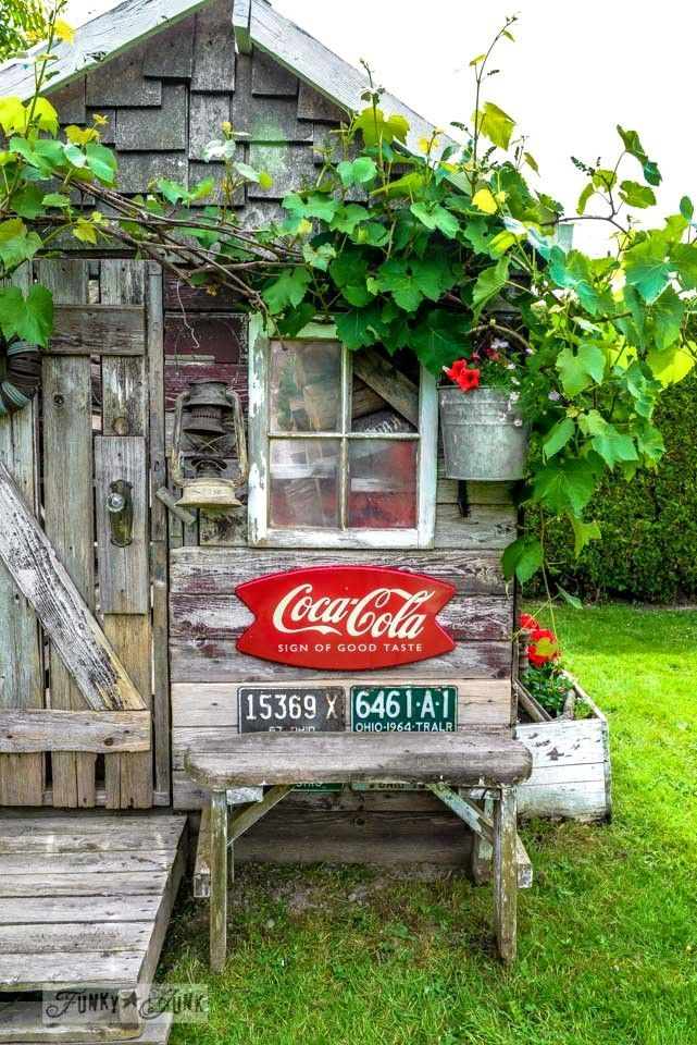 coke sign and vintage license plates rustic garden shed with old signs tools and